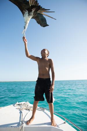 Kid feeds seagull boat travel belize Caribbean