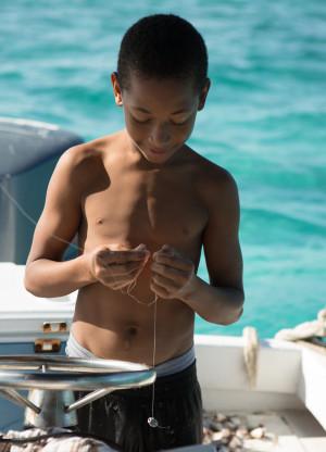 black kid prepares fishing pole in belize caribbean
