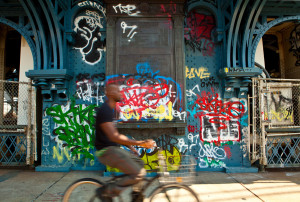 Biker rides by graffiti on middle of Manhattan Bridge, New York
