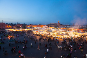 busy street travel scene at Djemaa el Fna at sunset in Marrakech
